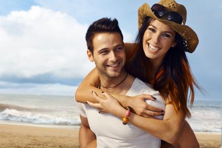 Happy loving couple having fun on the beach, enjoying summer holiday piggyback.