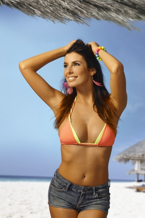 Beautiful young woman enjoying summer holiday on the beach in bikini, smiling happy. photo