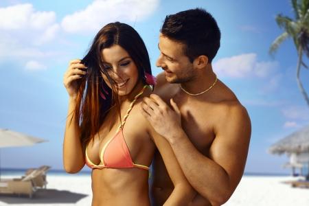 couple enlac�: Couple d'amoureux sexy embrassant sur la plage, sourire heureux.
