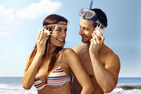 Happy loving couple on beach listening to murmur of sea in seashell, smiling. photo