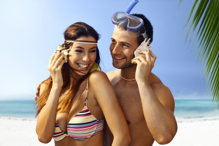 murmur: Happy young couple listening to murmur of sea in seashell on the beach, smiling, hugging.
