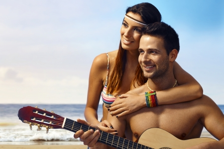 Loving couple enjoying summer holiday on the beach with guitar music.