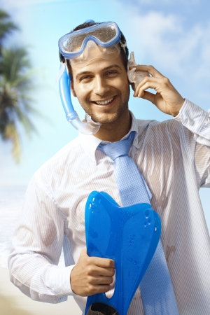 Happy businessman with scuba-diving equipments enjoying summer holiday, pretending to talking on mobile phone. photo