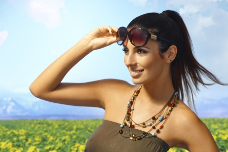Outdoor summer portrait of beautiful young woman in sunglasses on the meadows, smiling happy. photo
