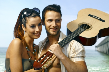 Romantic loving couple hugging on the coast, man holding guitar, smiling happy. photo