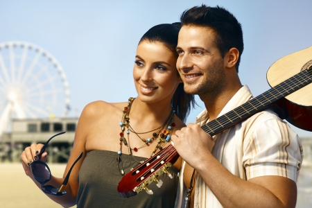 Summer portrait of happy smiling loving couple standing on the coast, man holding guitar. photo