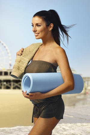 Pretty young girl walking on the beach with beach mattress and towel, smiling happy. photo