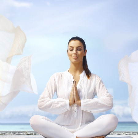 Happy smiling young woman meditating eyes closed on the coast in white outfit.