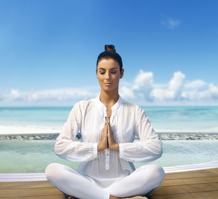 Young woman relaxing on the beach in prayer position, sitting eyes closed. Stock Photo - 19875881