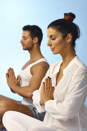 holistic view: Young couple meditating eyes closed in peace.