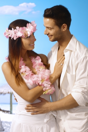 casual clothing: Young couple having exotic wedding on the beach, smiling happy, embracing. Stock Photo