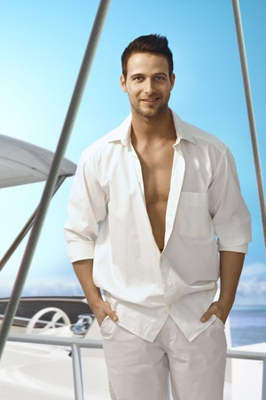 Summer portrait of handsome young man in white outfit standing on sailing boat, smiling happy. photo