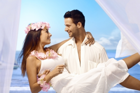 couple cuddling: Young man holding happy bride in arms after exotic wedding on tropical island. Stock Photo