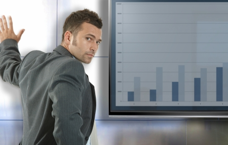 lcd: Young businessman doing presentation at meetingroom standing front of big LCD display, presenting charts. Stock Photo