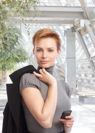 Outdoor portrait of attractive young businesswoman looking at camera, holding mobilephone. photo