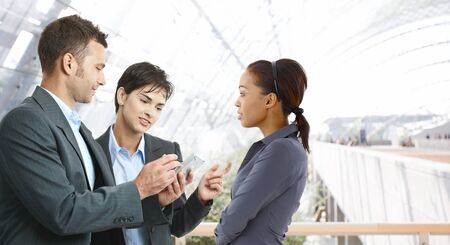palmtop: Young businesspeople talking at office lobby, using palmtop.