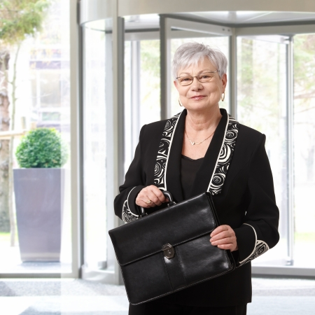 Portrait of elegant senior businesswoman holding briefcase. photo