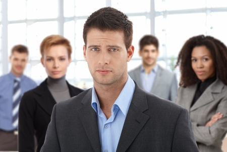 Closeup portrait of serious young businessman and team at office. photo