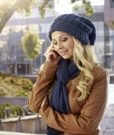 Pretty woman talking on mobilephone at autumn outdoors, wearing hat and scarf. photo