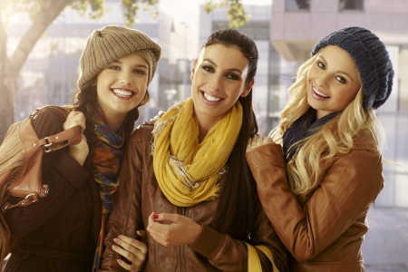 Outdoor portrait of three beautiful girls at autumn smiling happy, hugging. photo