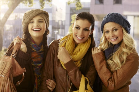 Three girls embracing outdoors at autumn, smiling. photo