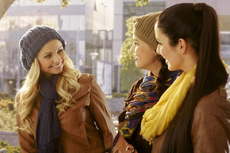 Three young girls walking together outdoors, chatting, smiling. photo
