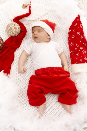 Infant sleeping in santa claus outfit among christmas ornaments. photo