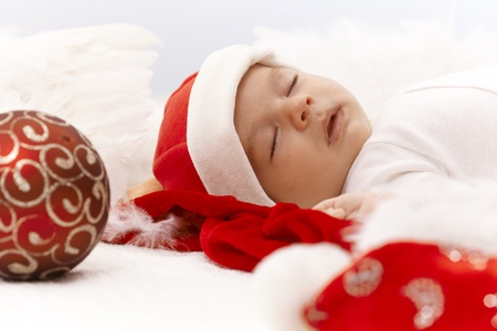 Closeup portrait of newborn baby sleeping in santa hat with christmas ornament. photo