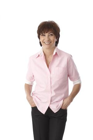 Portrait of mature woman standing hands in pockets, smiling happy. Stock fotó