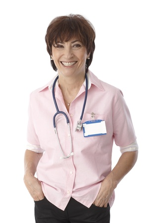 clinician: Portrait of happy smiling mature female doctor standing hands in pockets. Stock Photo