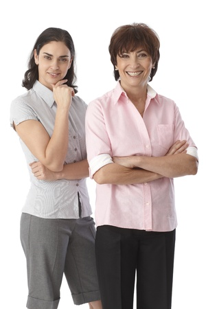 Happy mother and adult daughter standing arms crossed, smiling, looking at camera. photo