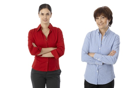 Two women, mother and daughter standing arms crossed, looking at camera, smiling over white background. photo