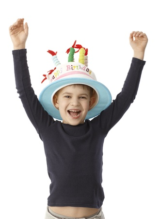 good looking boy: Little boy smiling happy on his birthday, wearing birthday cake hat with candles.