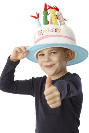 Happy little boy in birthday cake hat with thumb-up, smiling, looking at camera. photo