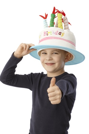 Cute little boy in birthday cake hat smiling happy with thumb up, looking at camera. photo