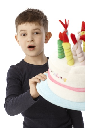 6 7 years: Portrait of little boy holding birthday cake hat, looking surprised.