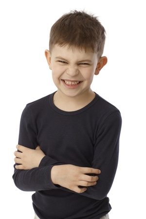 6 7 years: Little boy standing arms crossed showing his teeth, snarling, looking at camera. Stock Photo