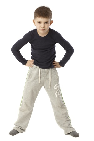 straddle: Little boy standing straddle with hands on hip, looking strict. Full size.