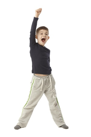 straddle: Little boy jittering, standing straddle, lifting right arm, shouting. Full size. Stock Photo