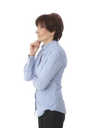 perfil de mujer rostro: Vista lateral de la empresaria madura, mirando a la derecha, pie con los brazos cruzados.