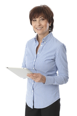 Happy senior woman standing, holding tablet computer, looking at camera. photo