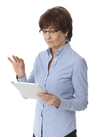 Mature woman using tablet computer, standing over white background.