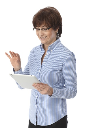 Senior woman using tablet computer, smiling over white background. photo
