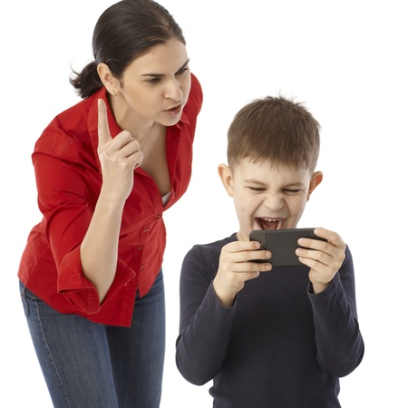 Little boy playing on mothers mobilephone, mother rebuking him. photo