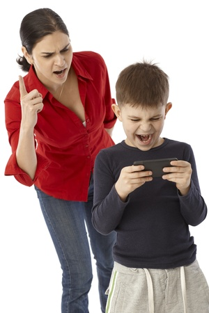 yell: Little boy playing with mothers mobilephone, angry mother warning with finger.