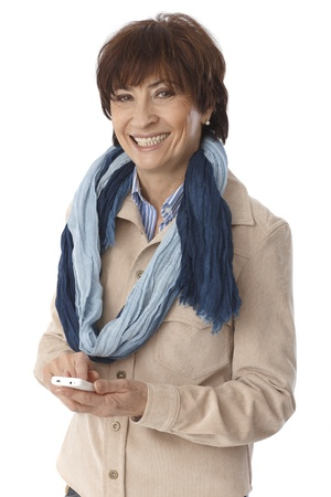 Elderly woman using mobilephone, smiling, looking at camera. photo