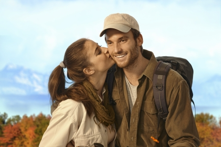 be kissed: Happy young couple hiking together in nice autumn weather, woman kissing man. Stock Photo