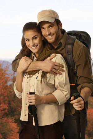 bonne aventure: Jeune couple randonnée dans la campagne d'automne, embrassant, tenue bâtons de marche. Banque d'images
