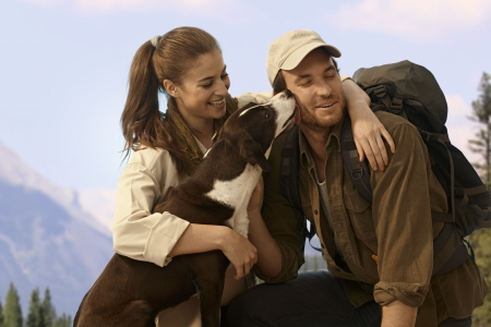 be kissed: Happy young hiking couple with dog outdoors.