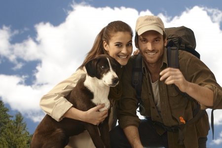 Portrait of happy young trekker couple with dog, looking at camera, smiling. photo